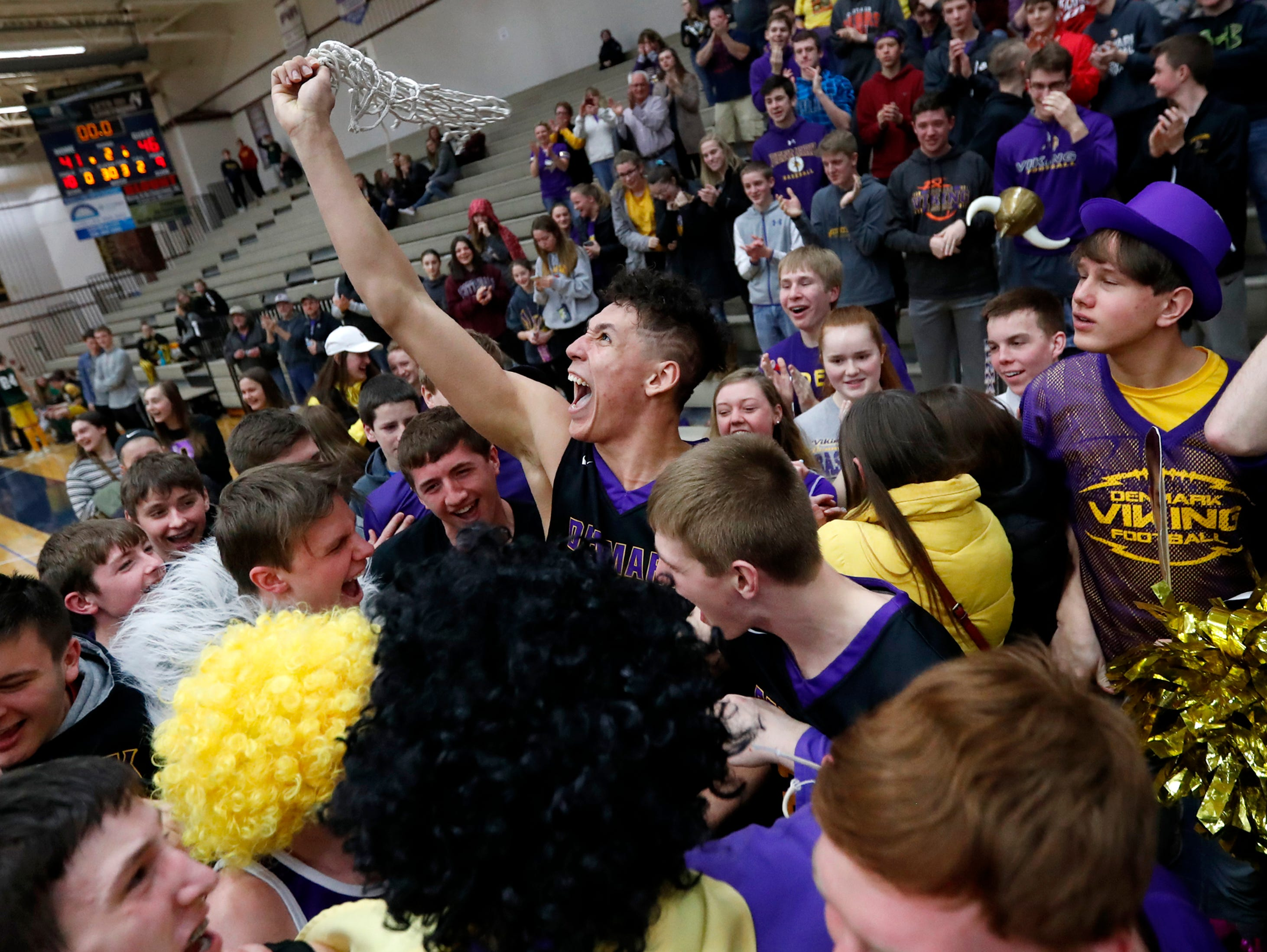 Denmark High SchoolÕs Patrick Suemnick waves the game net in a crowd of fans and players after their 46-41 win over Freedom High School in the D3 sectional final Saturday, March 9, 2019, at Appleton North High School in Appleton, Wis.Danny Damiani/USA TODAY NETWORK-Wisconsin