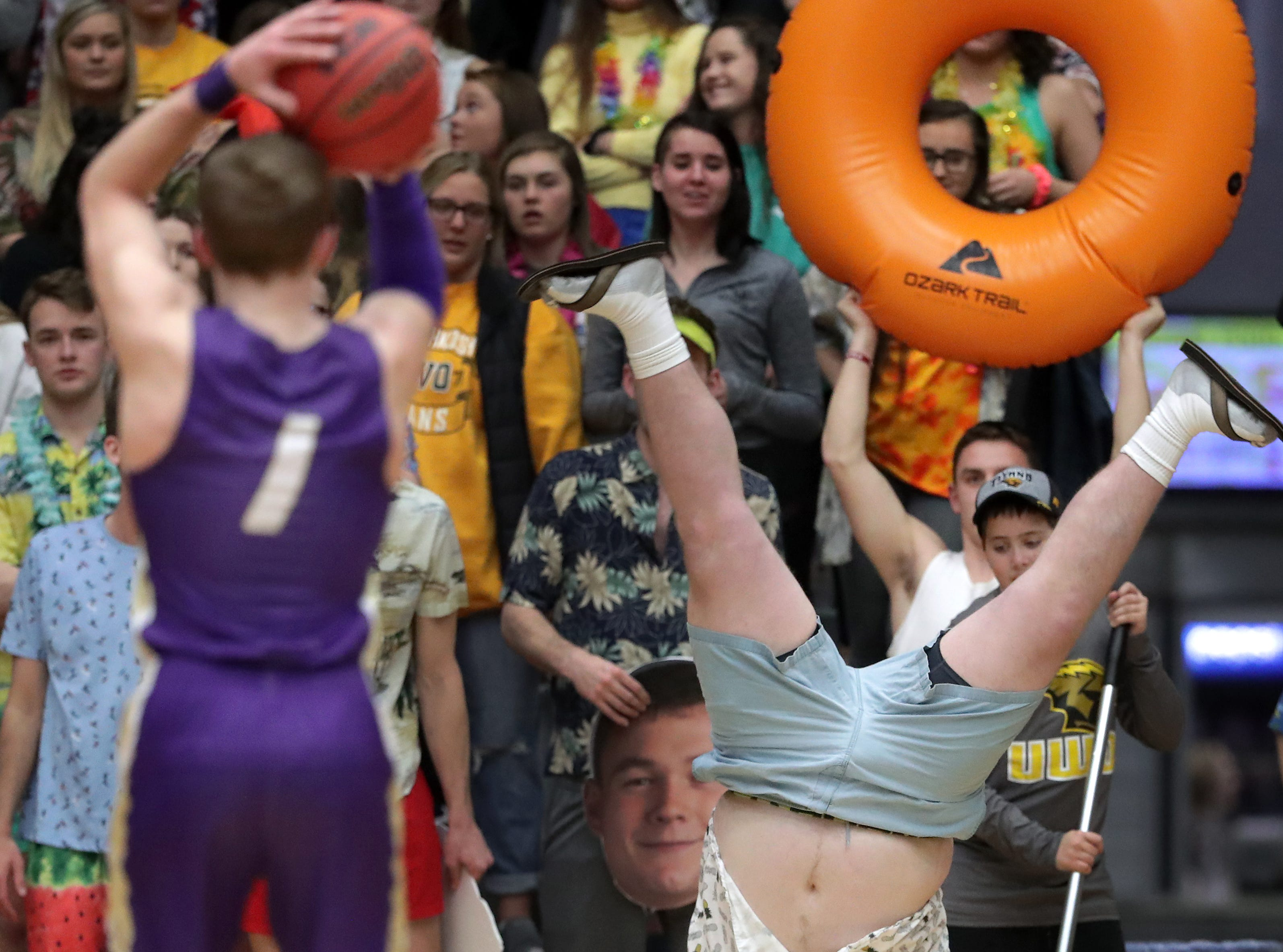 Nick Rooyakkers, University of Wisconsin-Oshkosh, does a cartwheel to distract Loras College-Iowa's, free throw shooting,  #1 Ryan DiCVanio during their NCAA DIII  Basketball Championship sectional game on Friday, March 8, 2019, at the Kolf Sports Center in Oshkosh, Wis. Oshkosh defeated Loras 86 to 75.Wm. Glasheen/USA TODAY NETWORK-Wisconsin.