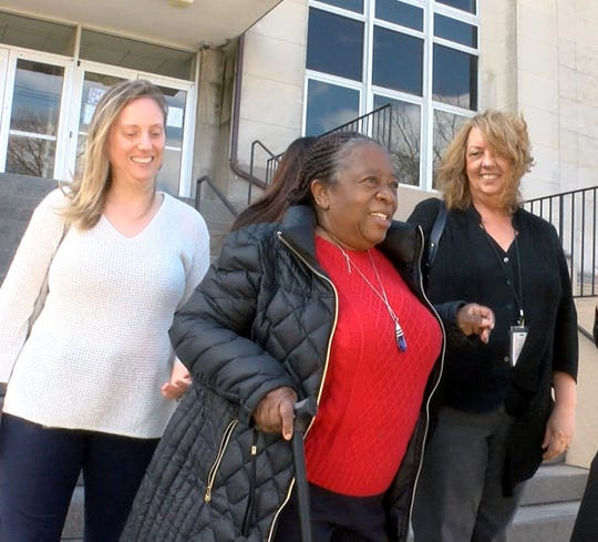 Jonelle Melton's mother Gwen Cruz (center) smiles as he leaves State Superior Court in Freehold after three men were found guilty of her daughter's murder Tuesday, March 12, 2019.