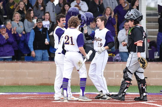Wylie's Brandon Sanders (19) is congratulated at home plate by Jaxon Hansen (39) and Cooper Cothran (21) after hitting a three-run home run against Aledo at Bulldog Field on Tuesday, March 12, 2019.