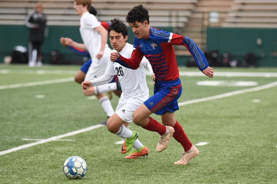Cooper's John Scaief (10) carries the ball past an Aledo defender at Shotwell Stadium on Monday, March 11, 2019. Scaief scored the first goal as the Cougars won 3-1