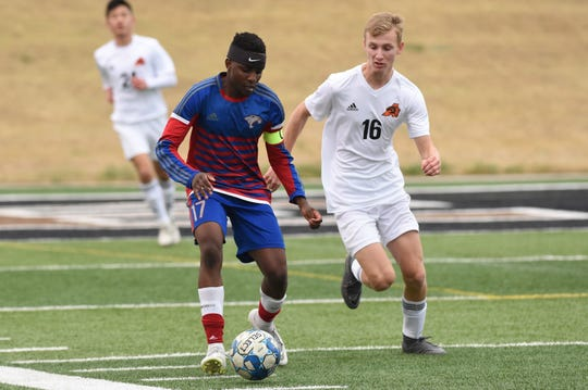 Cooper's Sylva Uwimana (17) turns away from an Aledo defender at Shotwell Stadium on Monday, March 11, 2019. The Cougars won 3-1.