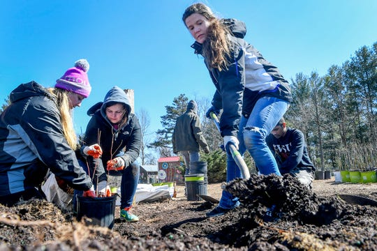 Abby Lawson, left, and RIley Darling pot a fruit tree as Caitlin Durkee scoops up dirt March 6, 2019 with Asheville GreenWorks.