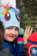 Dash Dorfman, 7, a first-grader at Rainbow Community School, places her hand on a beech tree on the school's property March 8, 2019 with her classmates. The tree was given a Treasured Tree honor.
