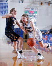 Battle Creek Harper Creek's Marley Bussler, right, drives against Haslett's Olivia Green, Monday, March 11, 2019, in Ionia, Mich. Haslett won 53-33.