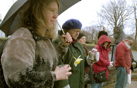 Kris Gilbert and Susan McAnanama, both of Binghamton, bow their heads in remembrance of the shooting victims during a peace vigi at Confluence Park in Binghamton.