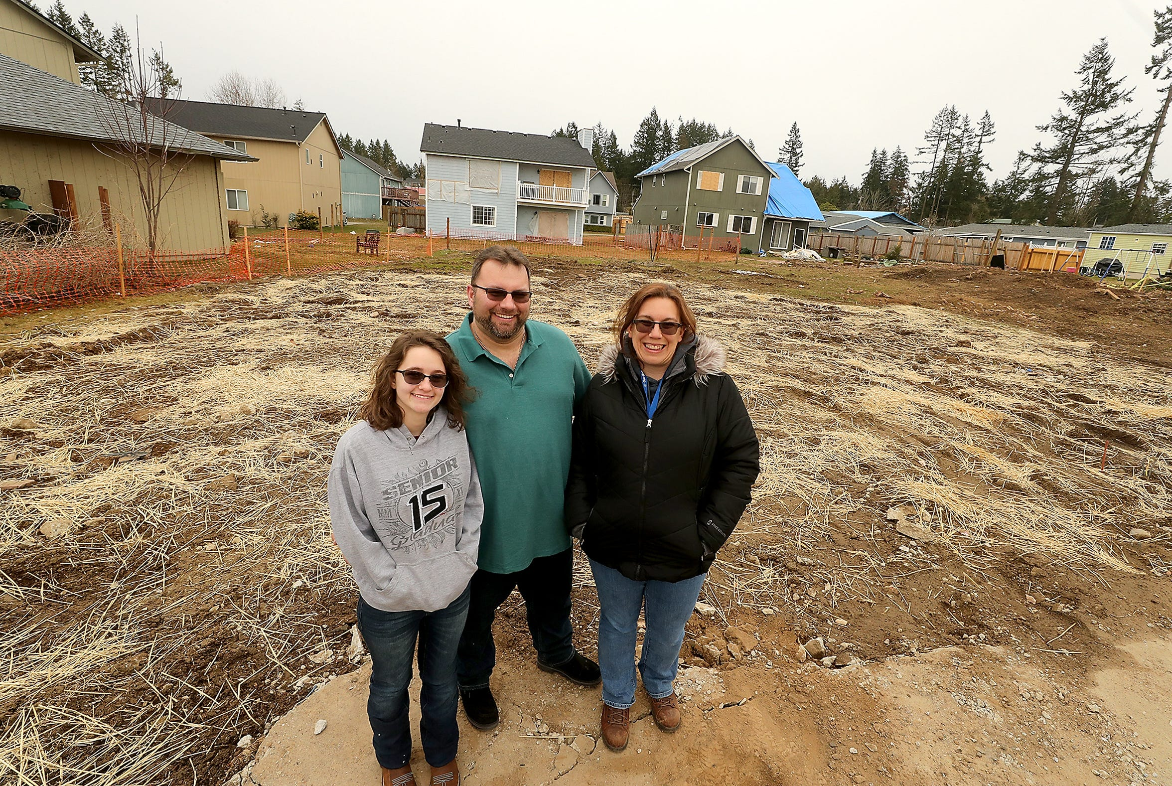 John and Beth Mueller with their daughter Jasmin, left, stand at the site where their home once stood on Tiburon Court in Port Orchard on Monday. The Muellers' home was destroyed during the December 2018 tornado when the storm ripped the entire roof off the structure, and it became well-known because news footage that documented their home without its roof spread far and wide.