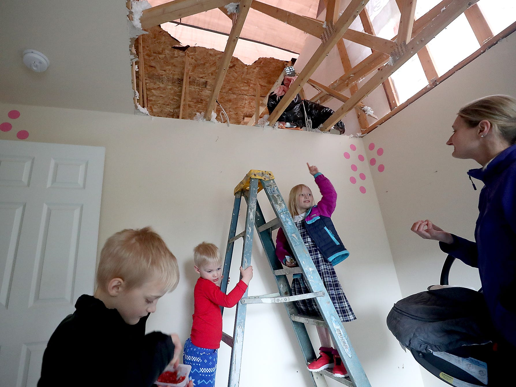 Julia Roscoe, 5, points to the missing ceiling in her bedroom while she and brother Benjamin, 3, stand on the bottom rungs of a ladder as they and their mother Liz (right) and brother Matthew, 7 (left) take a look at the repairs being done to their tornado damaged home on Kelby Circle in Port Orchard on Monday, March 11, 2019.