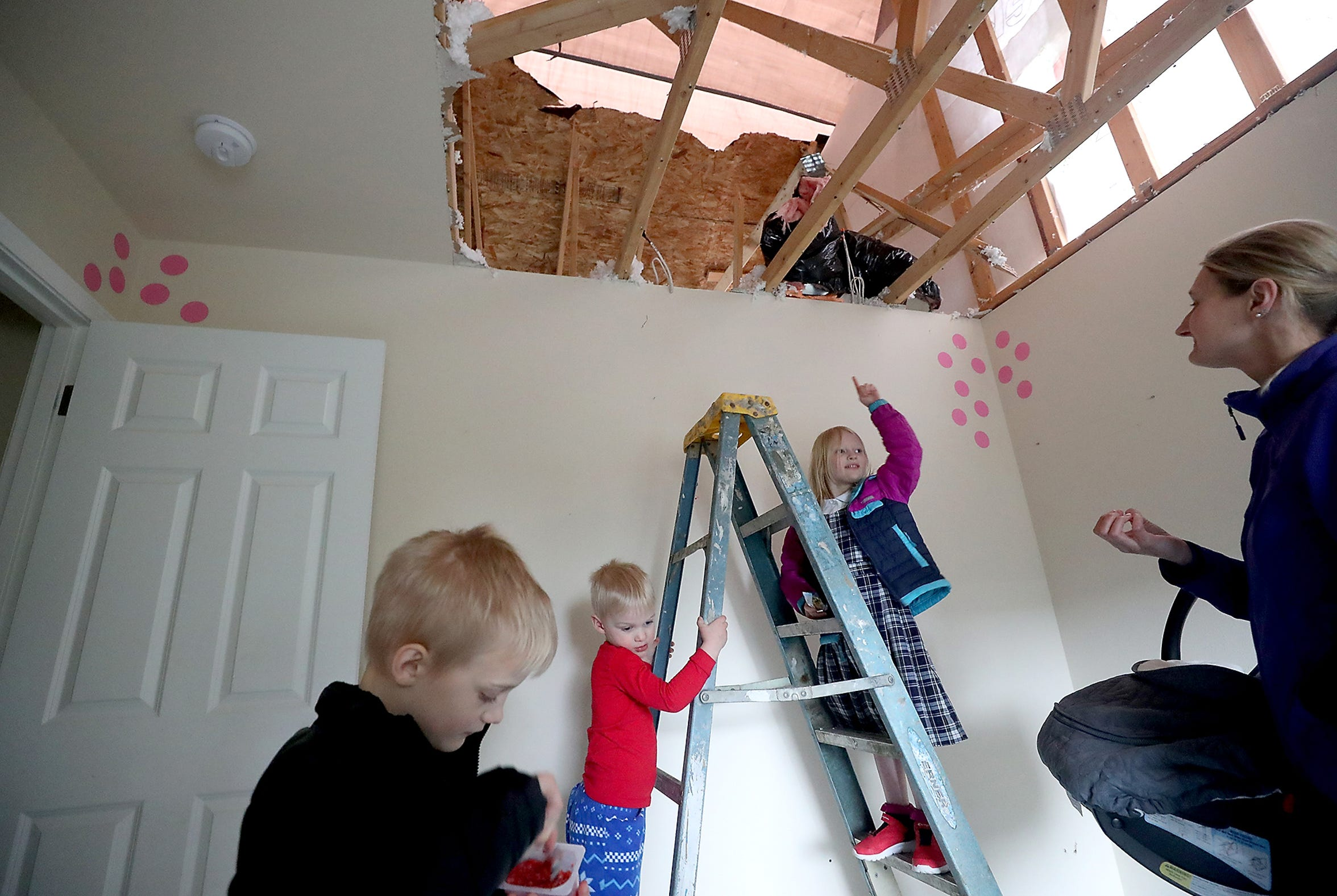 Julia Roscoe, 5, points to the missing ceiling in her bedroom while she and brother Benjamin, 3, stand on the bottom rungs of a ladder. Their mother Liz, right, and brother Matthew, 7, take a look at the repairs being done to their tornado-damaged home on Kelby Circle in Port Orchard on Monday.  Monday marks the three-month anniversary of the EF-2 tornado that touched down in Port Orchard on Dec. 18, 2018.