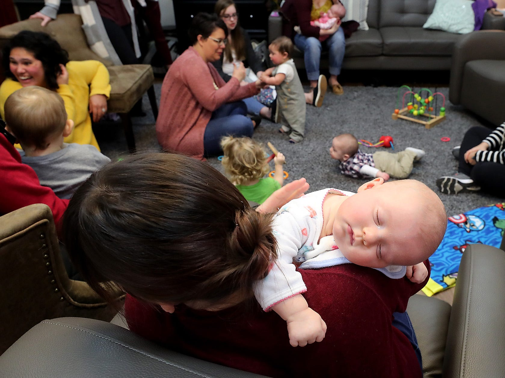 Three-month-old Eleanor Ray naps on the shoulder of her mom Tyne Tennyson-Ray during the Giggle & Grow Together group at Nurturing Expressions in Poulsbo on Tuesday, March 12, 2019.
