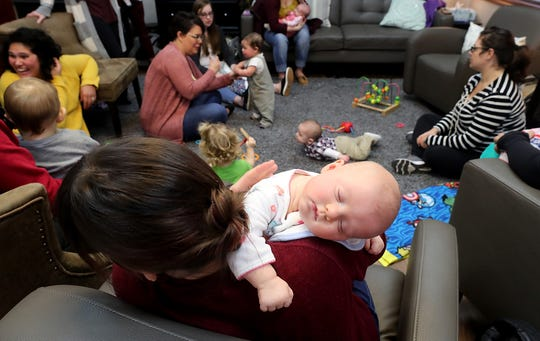Three-month-old Eleanor Ray naps on the shoulder of her mom, Tyne Tennyson-Ray, during the Giggle & Grow Together group at Nurturing Expressions in Poulsbo on Tuesday. Nurturing Expressions, which sells breast pumps and other items for newborns and babies, holds support groups for new moms and parents and is a vendor at the upcoming Peninsula Birth & Baby Expo.