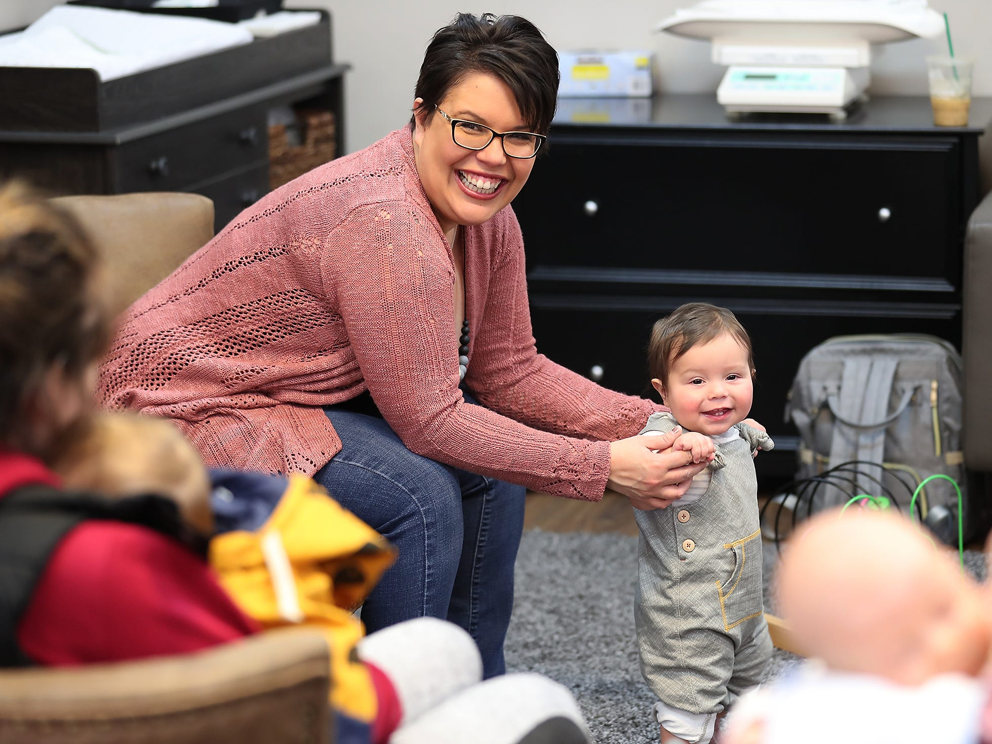 Elizabeth Montez helps 9-month-old son Langston Montez-Giras stand as she leads the Giggle & Grow Together group at Nurturing Expressions in Poulsbo on Tuesday, March 12, 2019.