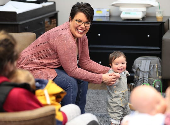 Elizabeth Montez helps her son, Langston Montez-Giras, stand as she leads the Giggle & Grow Together group at Nurturing Expressions in Poulsbo.