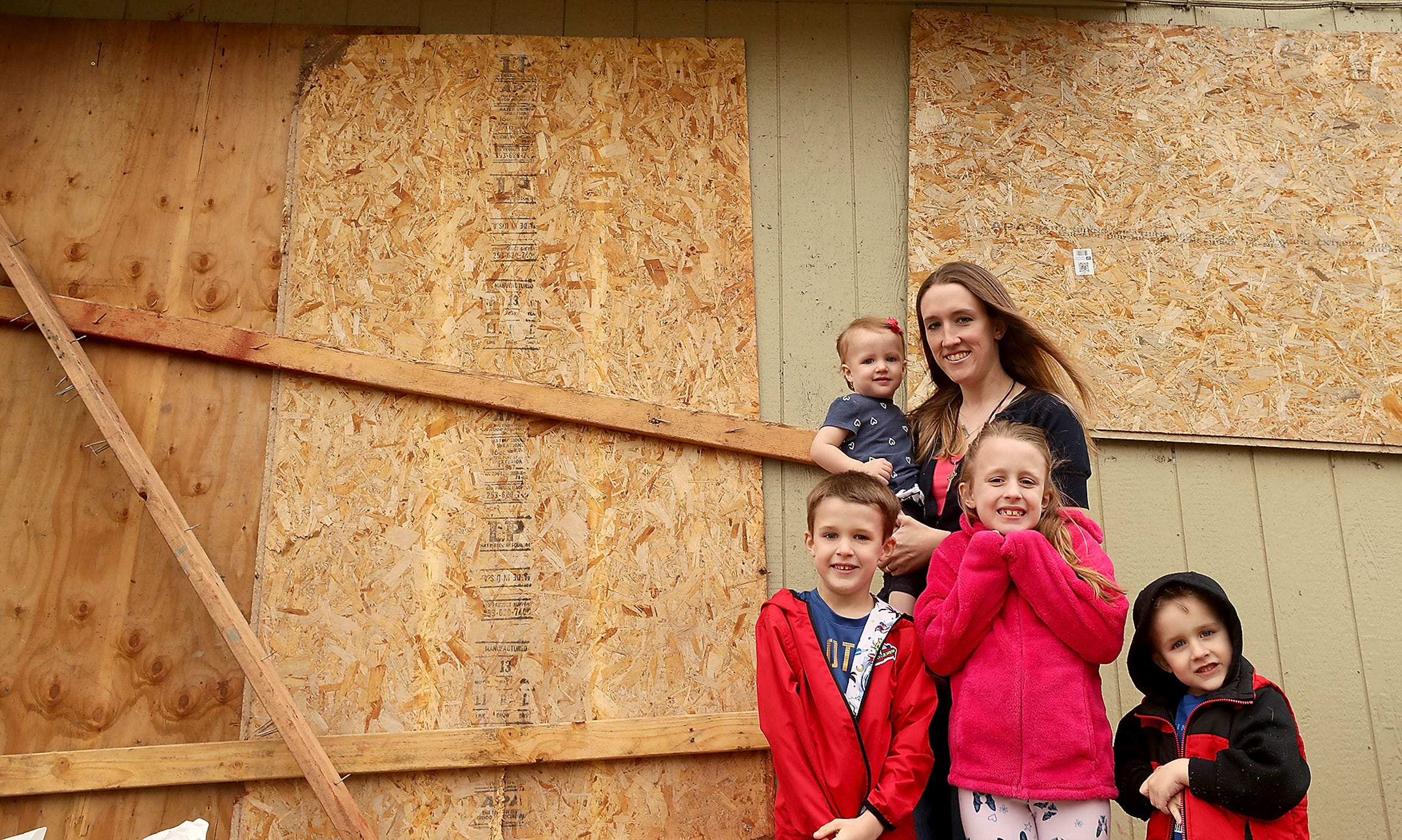 Courtney Watson with her kids (left to right) Solomon, 6, Kennedy, 1, Aislynn, 8, and Jude, 3, at their boarded-up Tiburon Court home in Port Orchard on Monday.