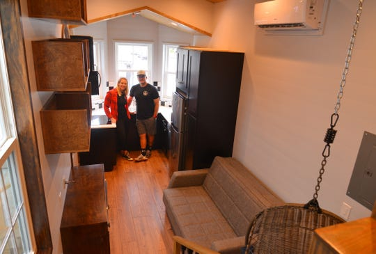 Mike and Nikki Cheatham stand inside a $120,000 Movable Roots tiny home they built for an autistic man who will live behind his parents' house in Pennsylvania.