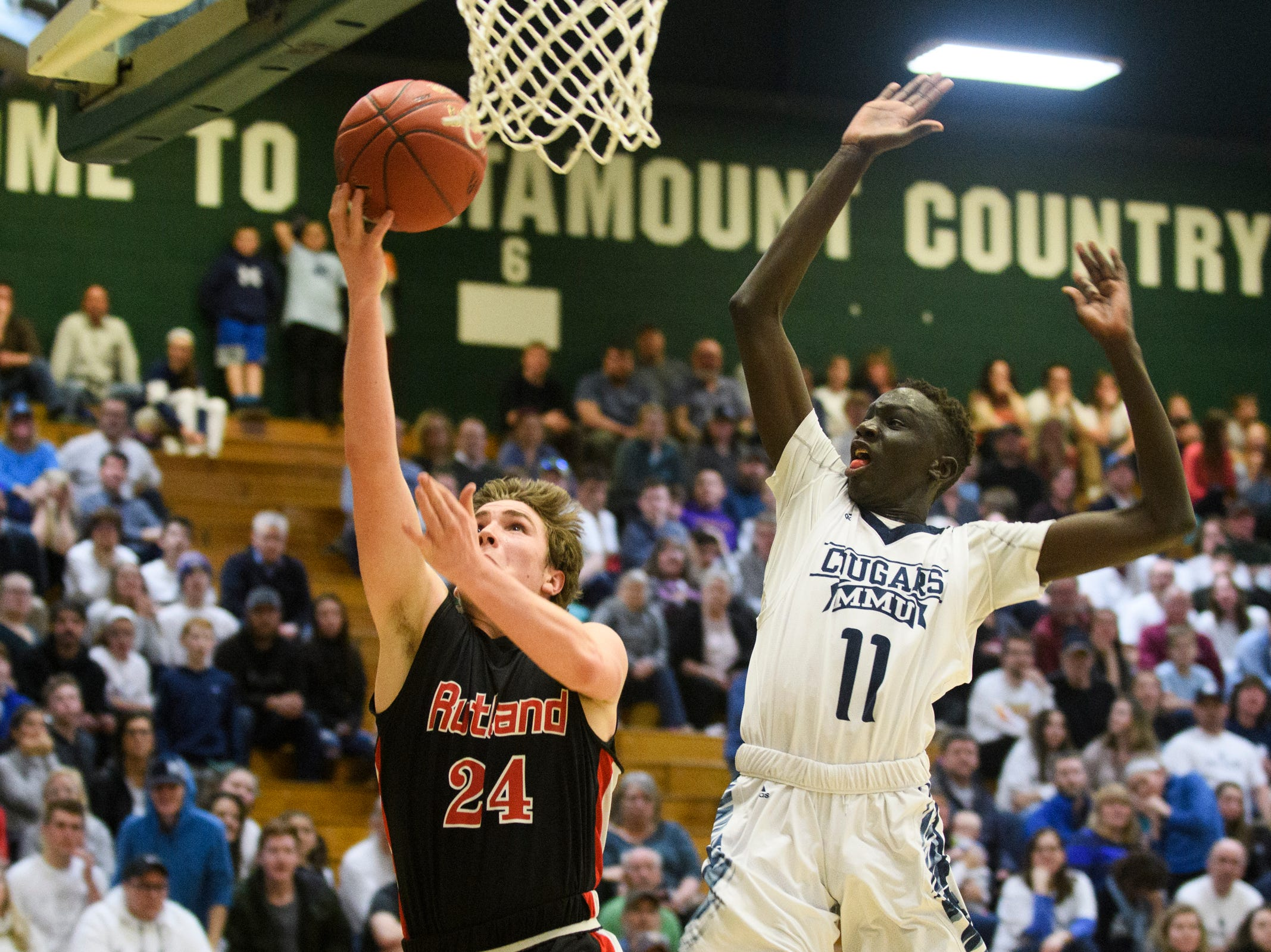 Rutland's Jacob Evans (24) leaps past MMU's Taylor Bowen (11) for a lay up during the boys DI semi final basketball game between the Rutland Raiders and the Mount Mansfield Cougars at Patrick Gym on Monday night March 11, 2019 in Burlington, Vermont.
