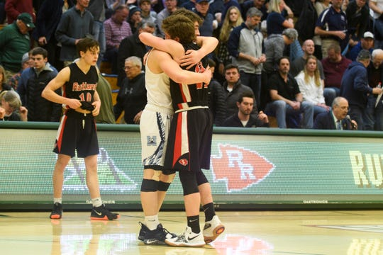 MMU's Harrison Leombruno-Nicholson (4) and Rutland's Jacob Lorman (24) hug at the conclusion of the boys DI semi final basketball game between the Rutland Raiders and the Mount Mansfield Cougars at Patrick Gym on Monday night March 11, 2019 in Burlington, Vermont.
