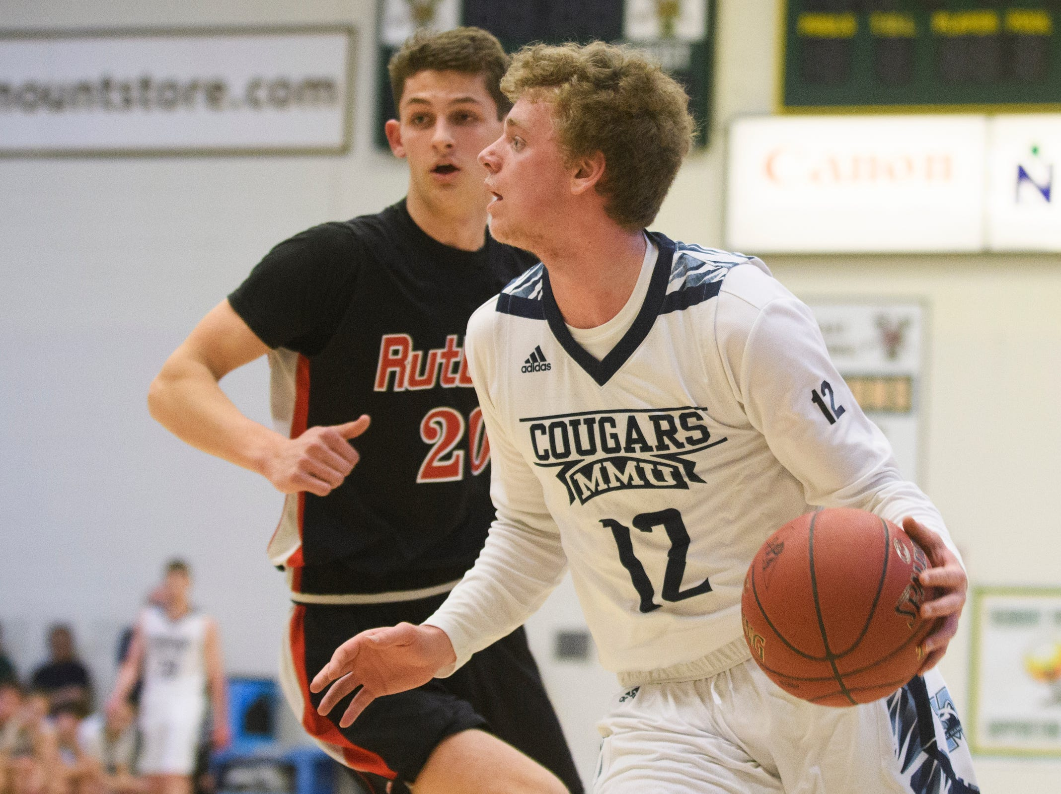 MMU's Asa Carlson (12) drives to the hoop during the boys DI semi final basketball game between the Rutland Raiders and the Mount Mansfield Cougars at Patrick Gym on Monday night March 11, 2019 in Burlington, Vermont.