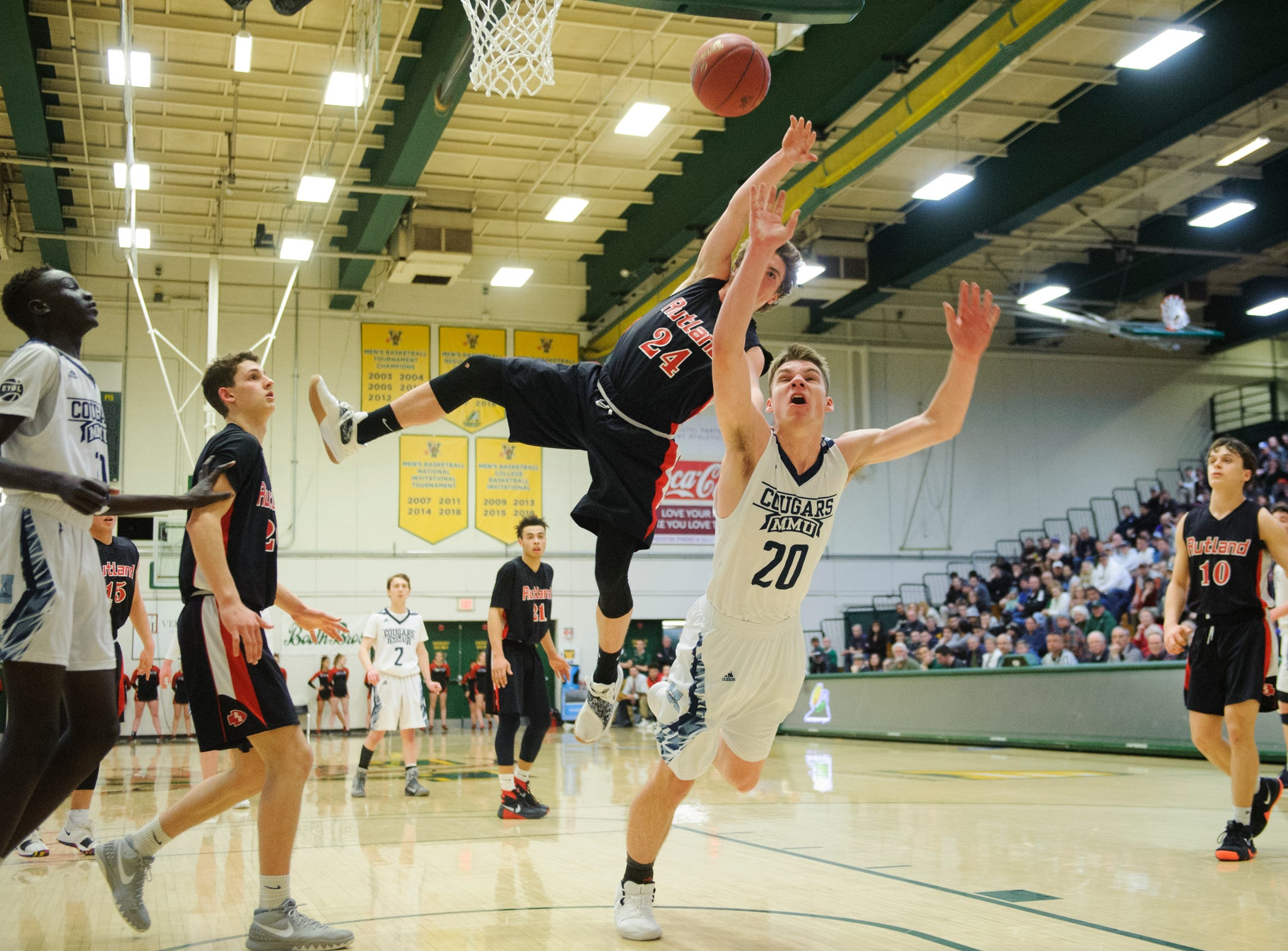 Rutland's Jacob Lorman (24) fouls MMU's Connor Philbrick (20) as he leaps for a lay up during the boys DI semi final basketball game between the Rutland Raiders and the Mount Mansfield Cougars at Patrick Gym on Monday night March 11, 2019 in Burlington, Vermont.