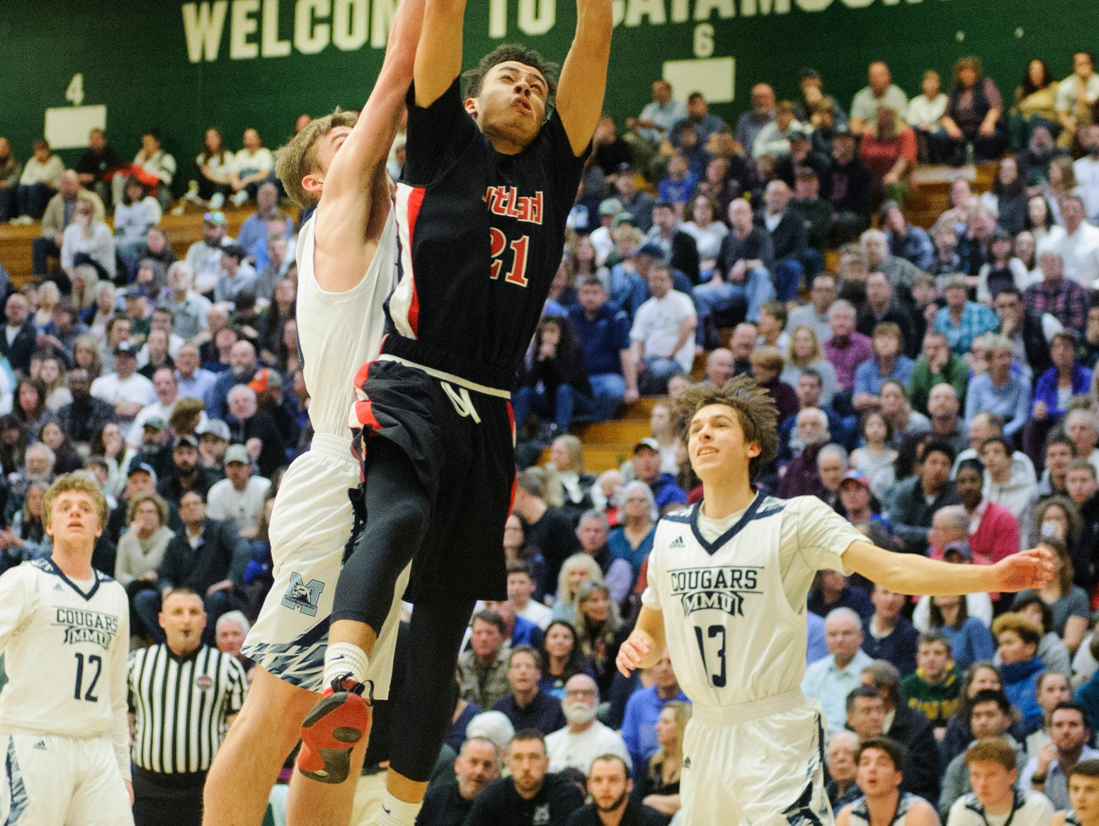 Rutland's Jamison Evans (21) leaps for a lay up during the boys DI semi final basketball game between the Rutland Raiders and the Mount Mansfield Cougars at Patrick Gym on Monday night March 11, 2019 in Burlington, Vermont.