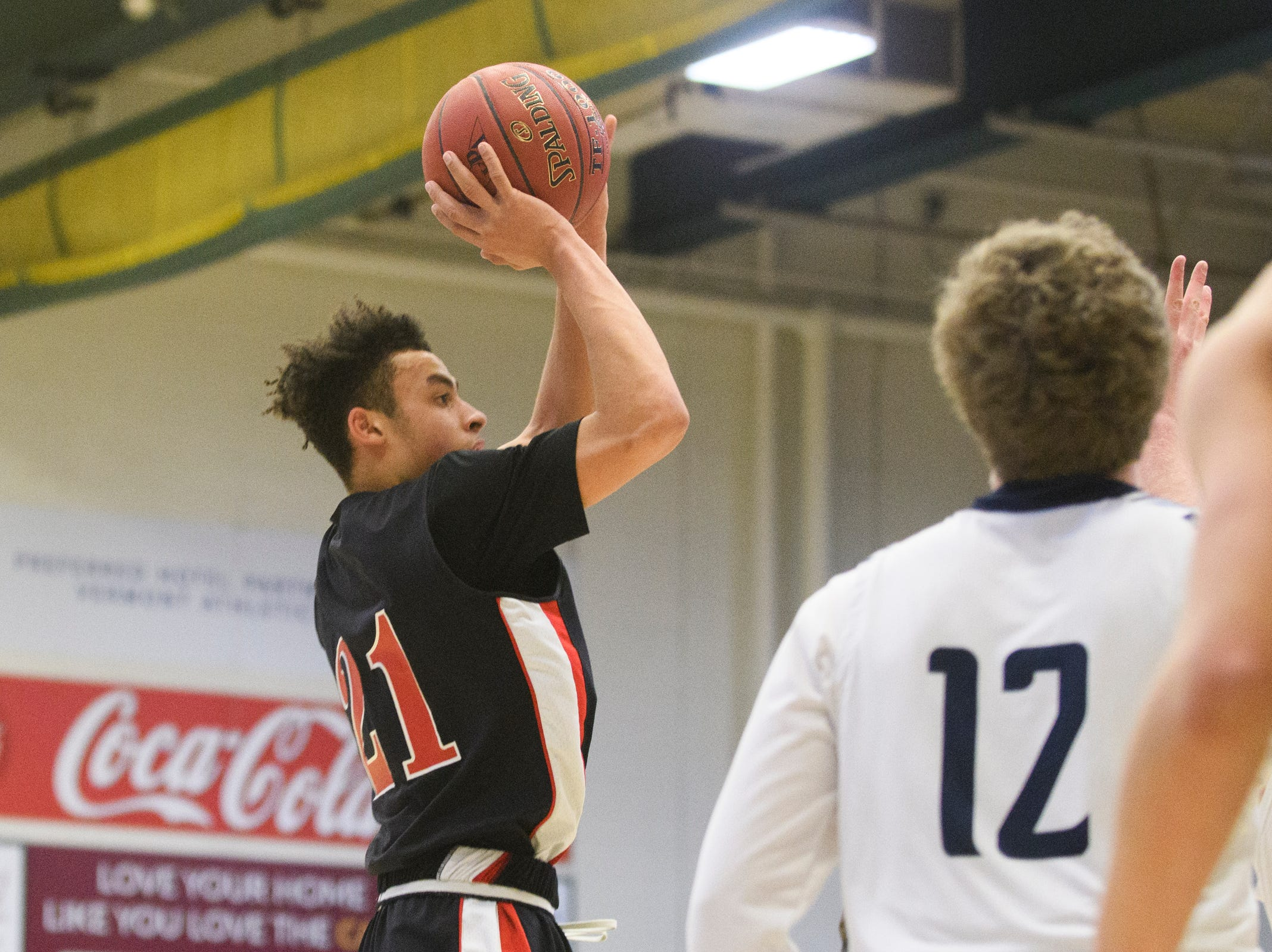 Rutland's Jamison Evans (21) shoots the ball during the boys DI semi final basketball game between the Rutland Raiders and the Mount Mansfield Cougars at Patrick Gym on Monday night March 11, 2019 in Burlington, Vermont.
