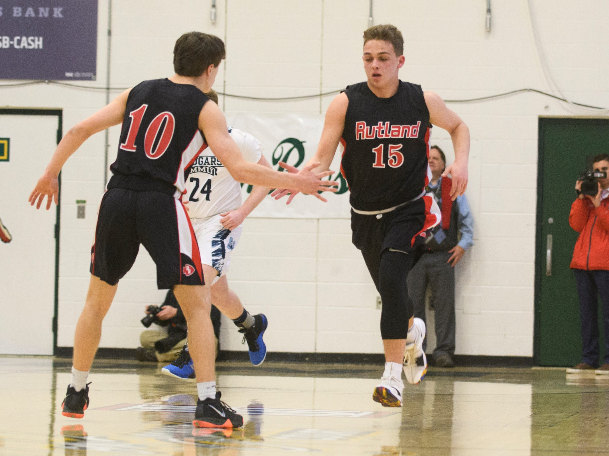 Rutland's Ethan Notte (15) and Evan Pocket (10) celebrates a three pointer during the boys DI semi final basketball game between the Rutland Raiders and the Mount Mansfield Cougars at Patrick Gym on Monday night March 11, 2019 in Burlington, Vermont.