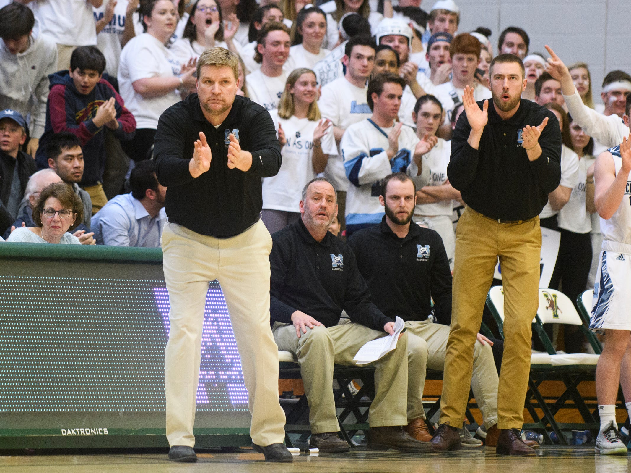 MMU head coach Jeff Davis cheers for the team during the boys DI semi final basketball game between the Rutland Raiders and the Mount Mansfield Cougars at Patrick Gym on Monday night March 11, 2019 in Burlington, Vermont.
