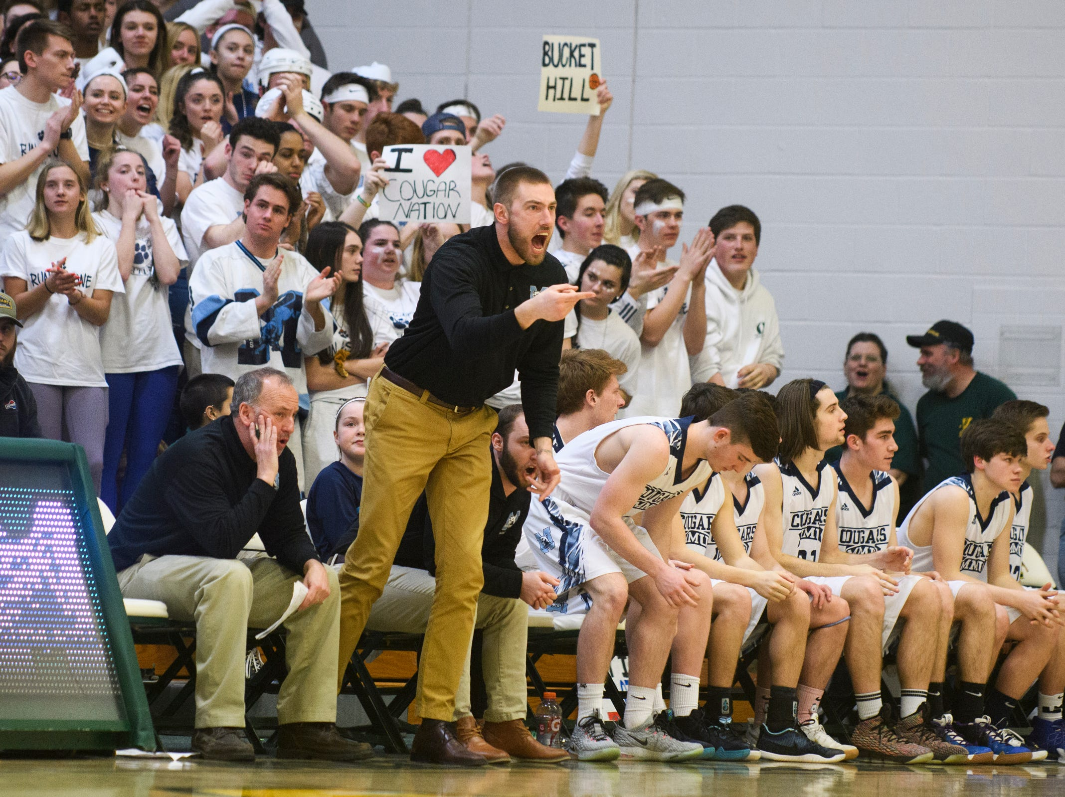 MMU coach Matt Glass talks to the team on the court during the boys DI semi final basketball game between the Rutland Raiders and the Mount Mansfield Cougars at Patrick Gym on Monday night March 11, 2019 in Burlington, Vermont.