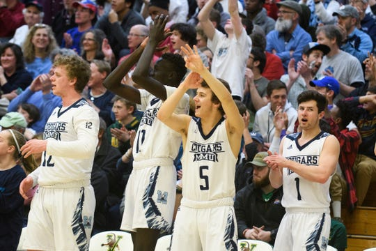 The MMU bench celebrates a three pointer during the boys DI semi final basketball game between the Rutland Raiders and the Mount Mansfield Cougars at Patrick Gym on Monday night March 11, 2019 in Burlington, Vermont.