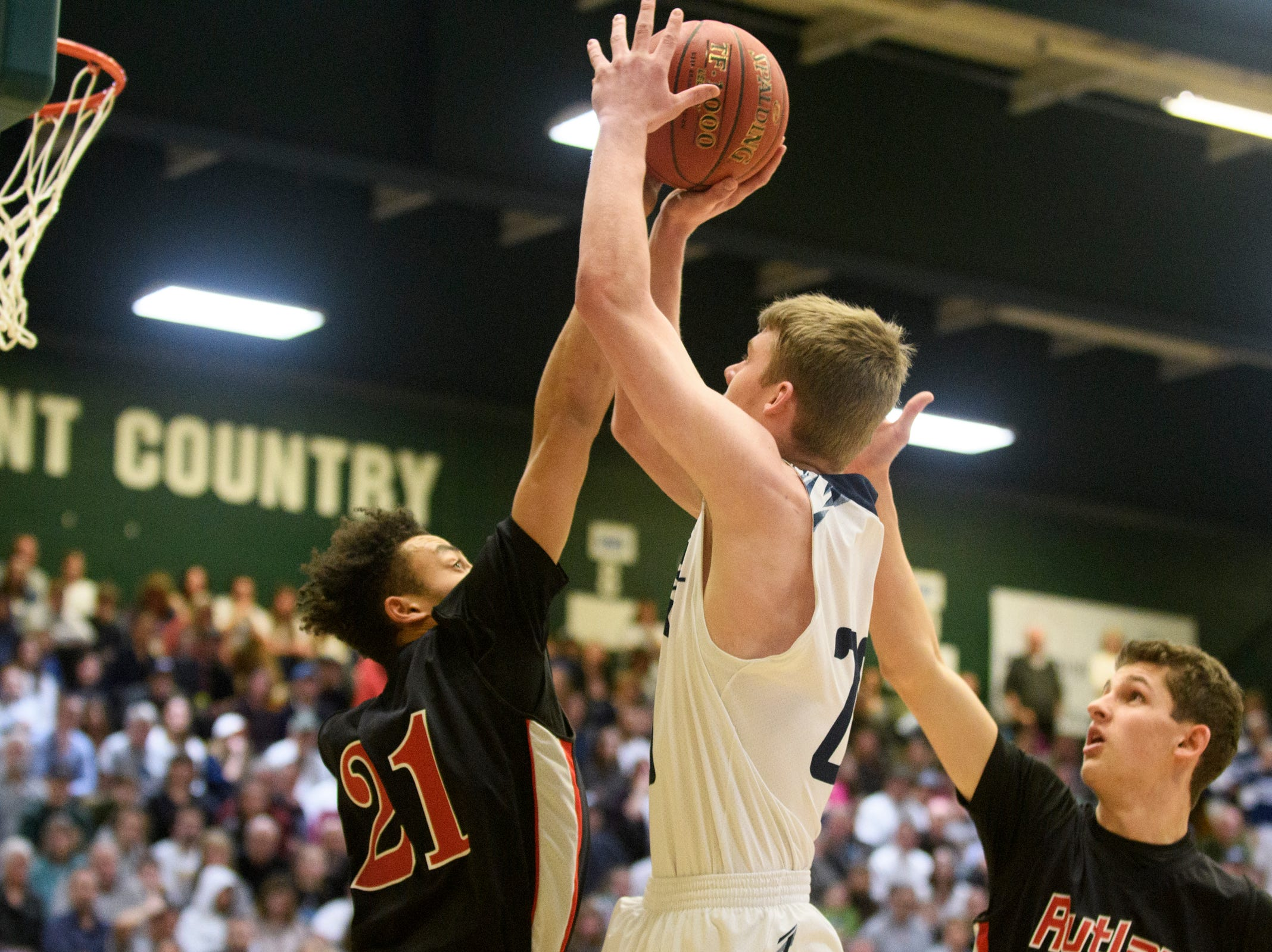 MMU's Connor Philbrick (20) leaps to take a shot over Rutland's Jameson Evans (21) during the boys DI semi final basketball game between the Rutland Raiders and the Mount Mansfield Cougars at Patrick Gym on Monday night March 11, 2019 in Burlington, Vermont.