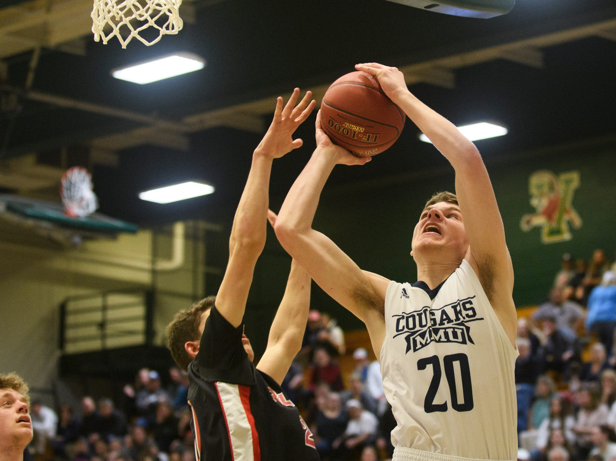 MMU's Connor Philbrick (20) leaps to take a shot during the boys DI semi final basketball game between the Rutland Raiders and the Mount Mansfield Cougars at Patrick Gym on Monday night March 11, 2019 in Burlington, Vermont.