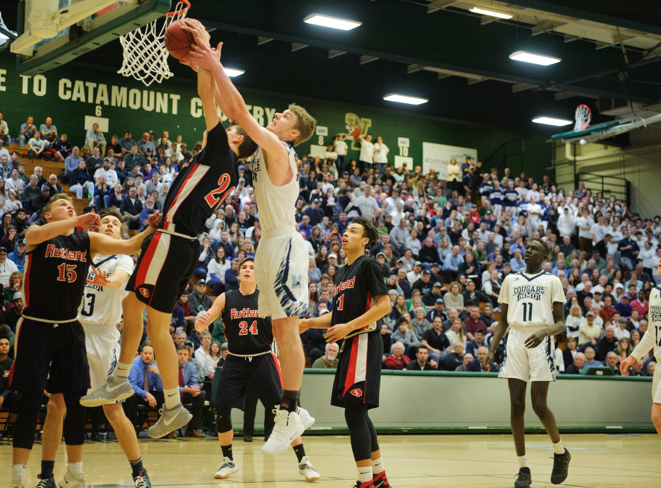Rutland's Eric Coughlin (20) and MMU's Connor Philbrick (20) battle for the rebound during the boys DI semi final basketball game between the Rutland Raiders and the Mount Mansfield Cougars at Patrick Gym on Monday night March 11, 2019 in Burlington, Vermont.