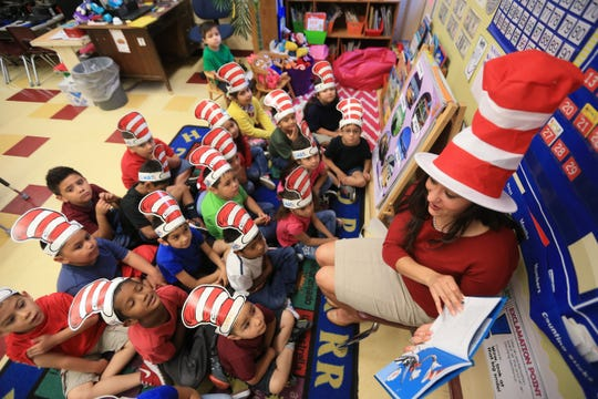 Michelle Unda, an employee with NuStar Energy, reads to kindergarten students at Houston Elementary School on Wednesday, March 2, 2016. The United Way of the Coastal Bend held a reading event at the school to celebrate Dr. Seuss' Birthday.
