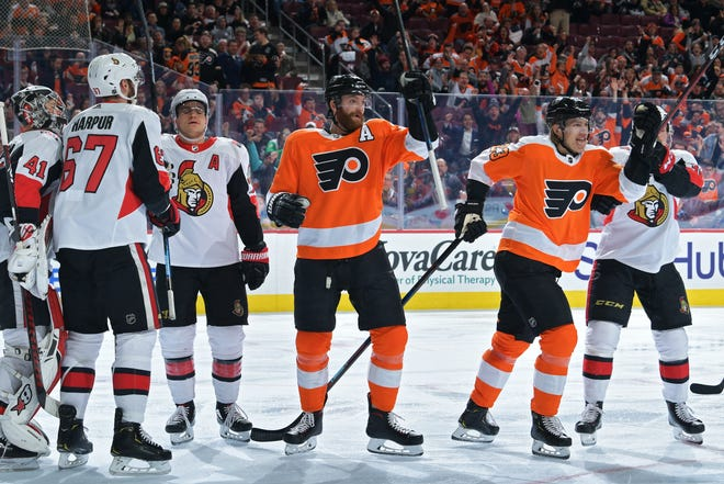 PHILADELPHIA, PENNSYLVANIA - MARCH 11: Sean Couturier #14 and Oskar Lindblom #23 of the Philadelphia Flyers celebrate as Craig Anderson #41, Brady Tkachuk #7 and Mark Borowiecki #74 of the Ottawa Senators react in the second period at Wells Fargo Center on March 11, 2019 in Philadelphia, Pennsylvania. (Photo by Drew Hallowell/Getty Images)