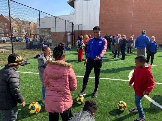 FC Cincinnati right back Alvas Powell leads West End children in soccer juggling drills.