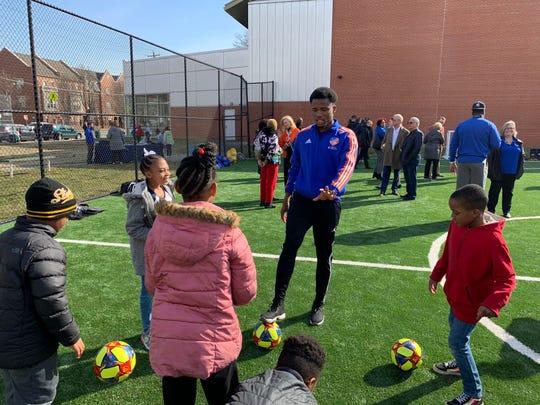 FC Cincinnati right back Alvas Powell leads West End children in soccer juggling drills.