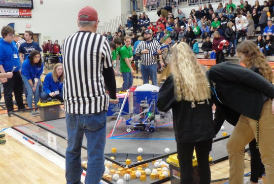 Dayton Innovator Robotics team 3311 and alliance members look on as their robot competes in a final qualifying round of the state championship tournamen at Loveland High School.