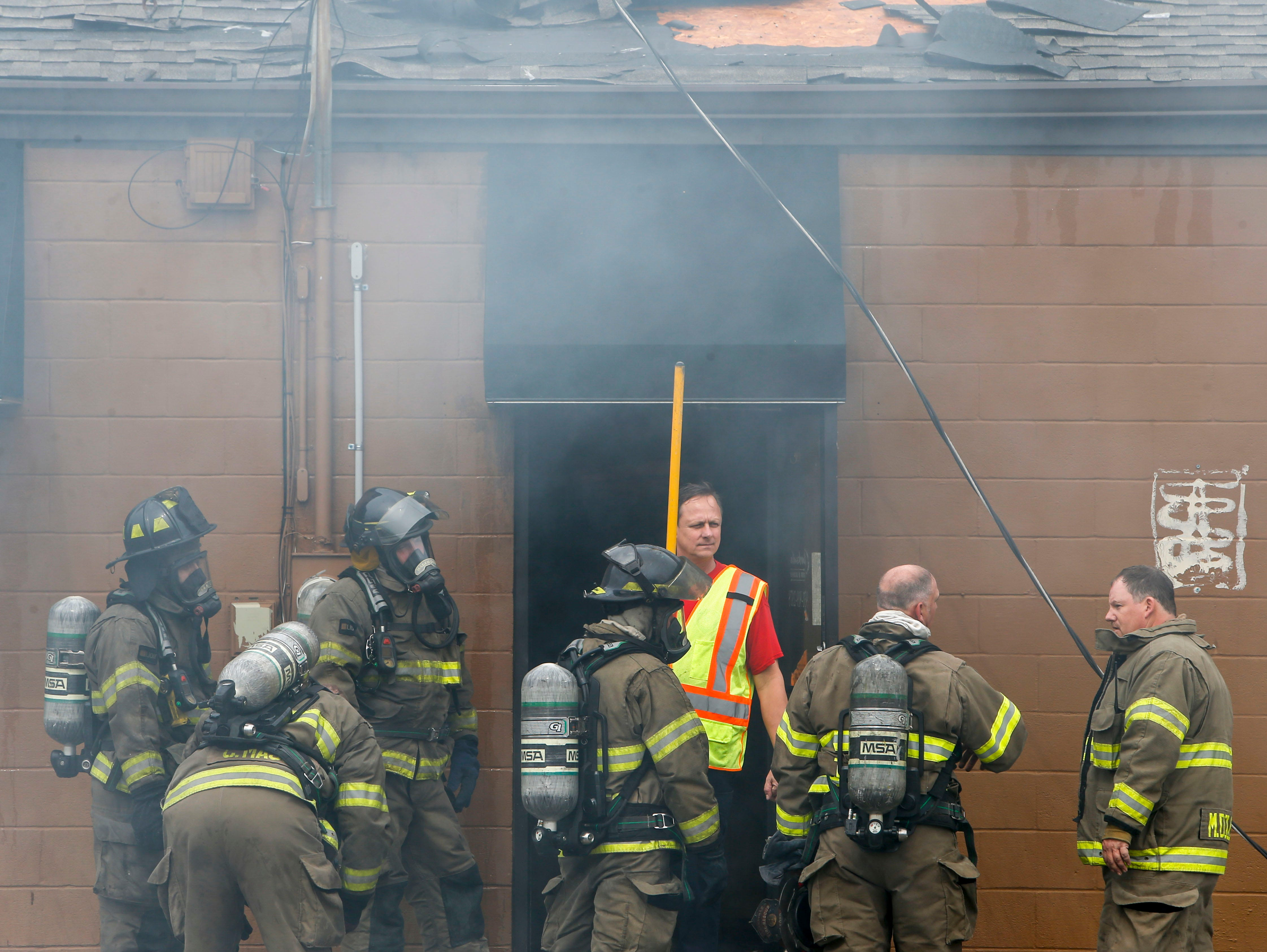 Clarksville Fire Rescue responders gather at the doorway of the shooting range before moving in for another sweep at Clarksville Guns & Archery in Clarksville, Tenn., on Tuesday, March 12, 2019.