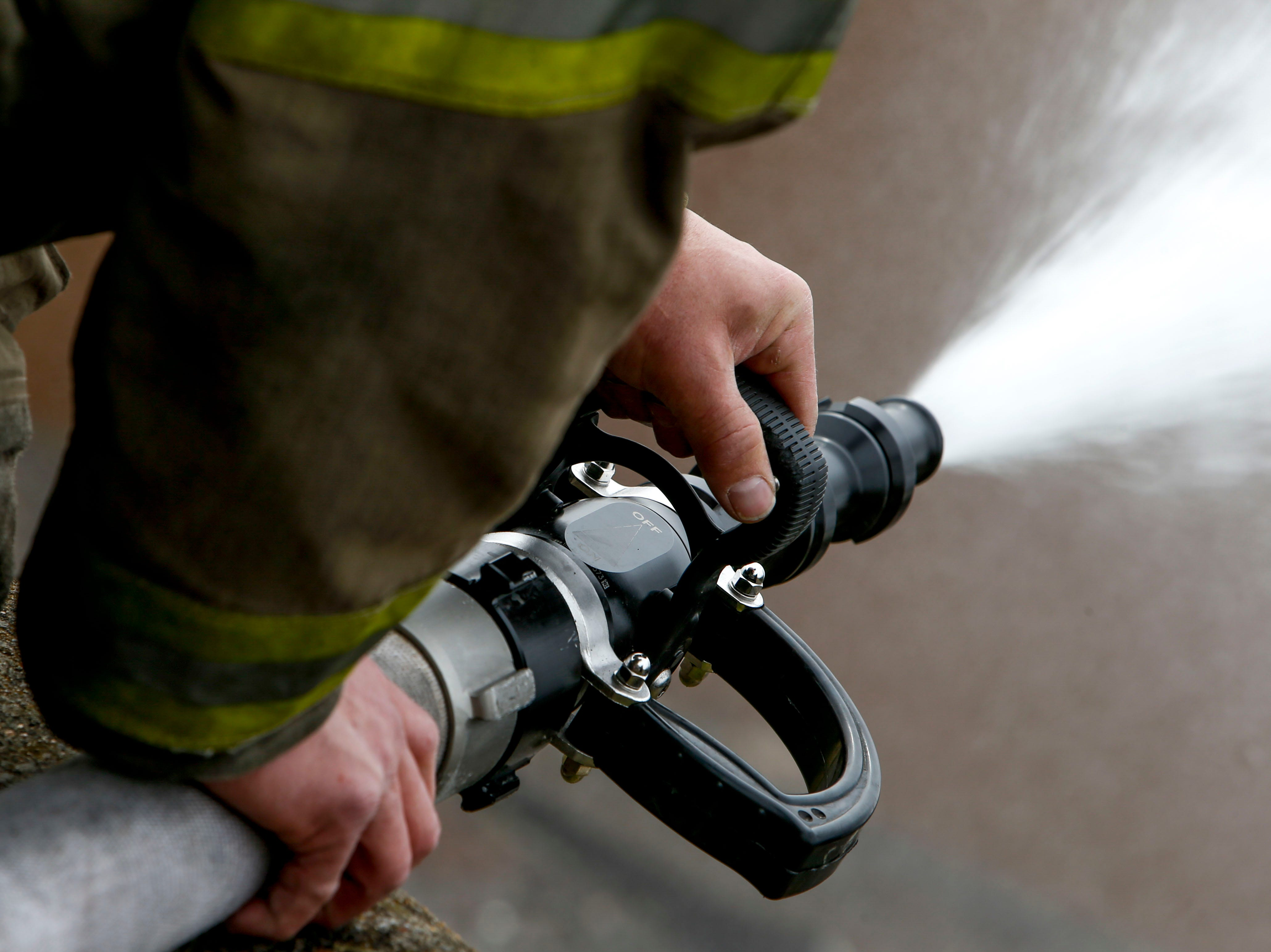 A Clarksville Fire Rescue firefighter holds down a hose while working to put out a fire in the shooting range at Clarksville Guns & Archery in Clarksville, Tenn., on Tuesday, March 12, 2019.