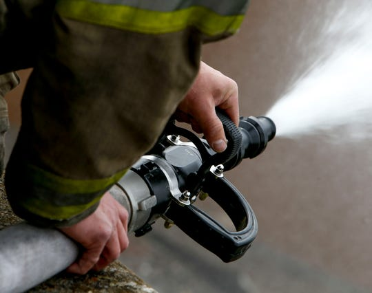 A Clarksville Fire Rescue firefighter holds down a hose while working to put out a fire in Clarksville, Tenn.