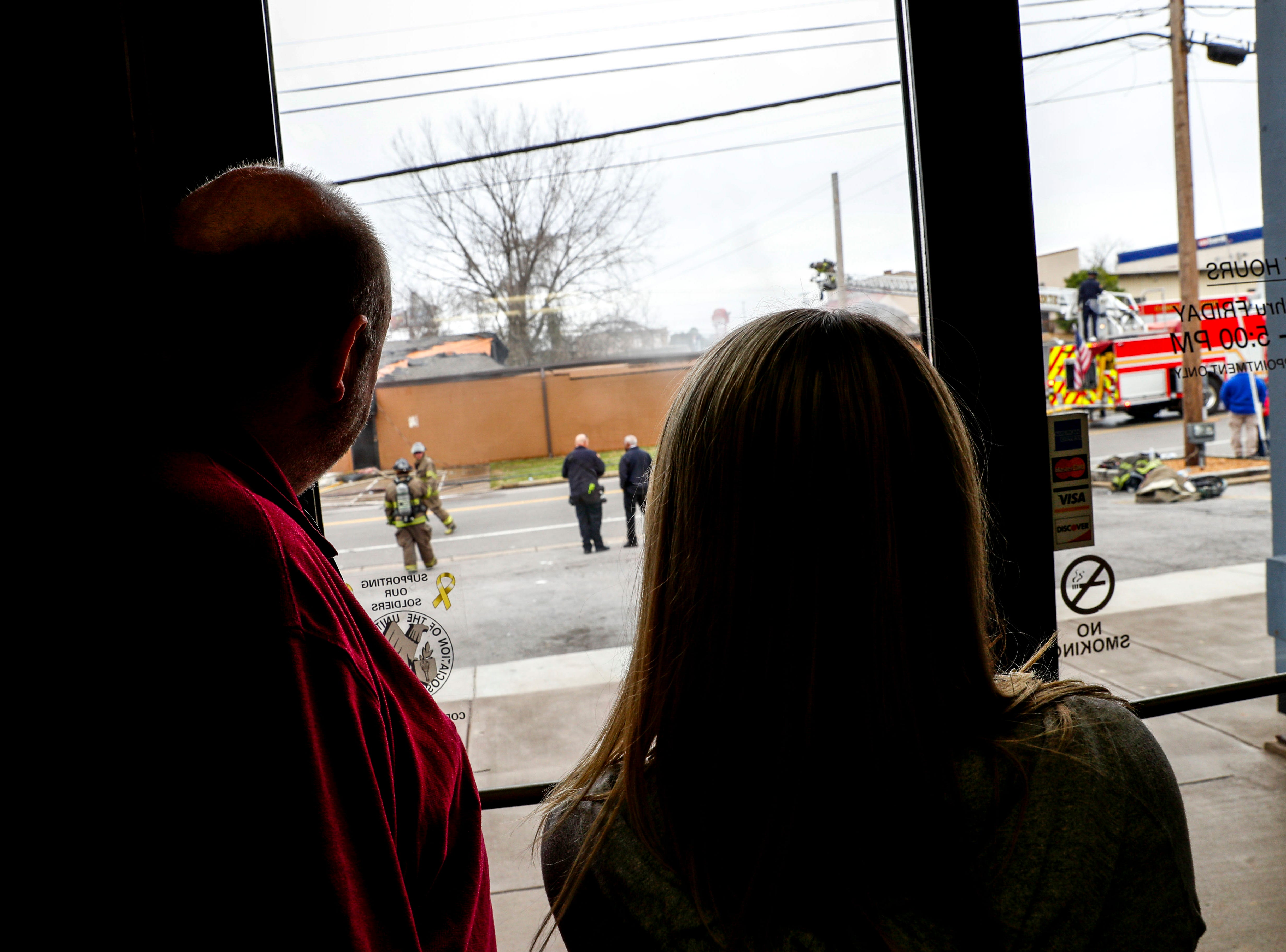 Employees of Thomas Lumber Co across the street watch as Clarksville Fire Rescue responders work to put out the fire at Clarksville Guns & Archery in Clarksville, Tenn., on Tuesday, March 12, 2019.