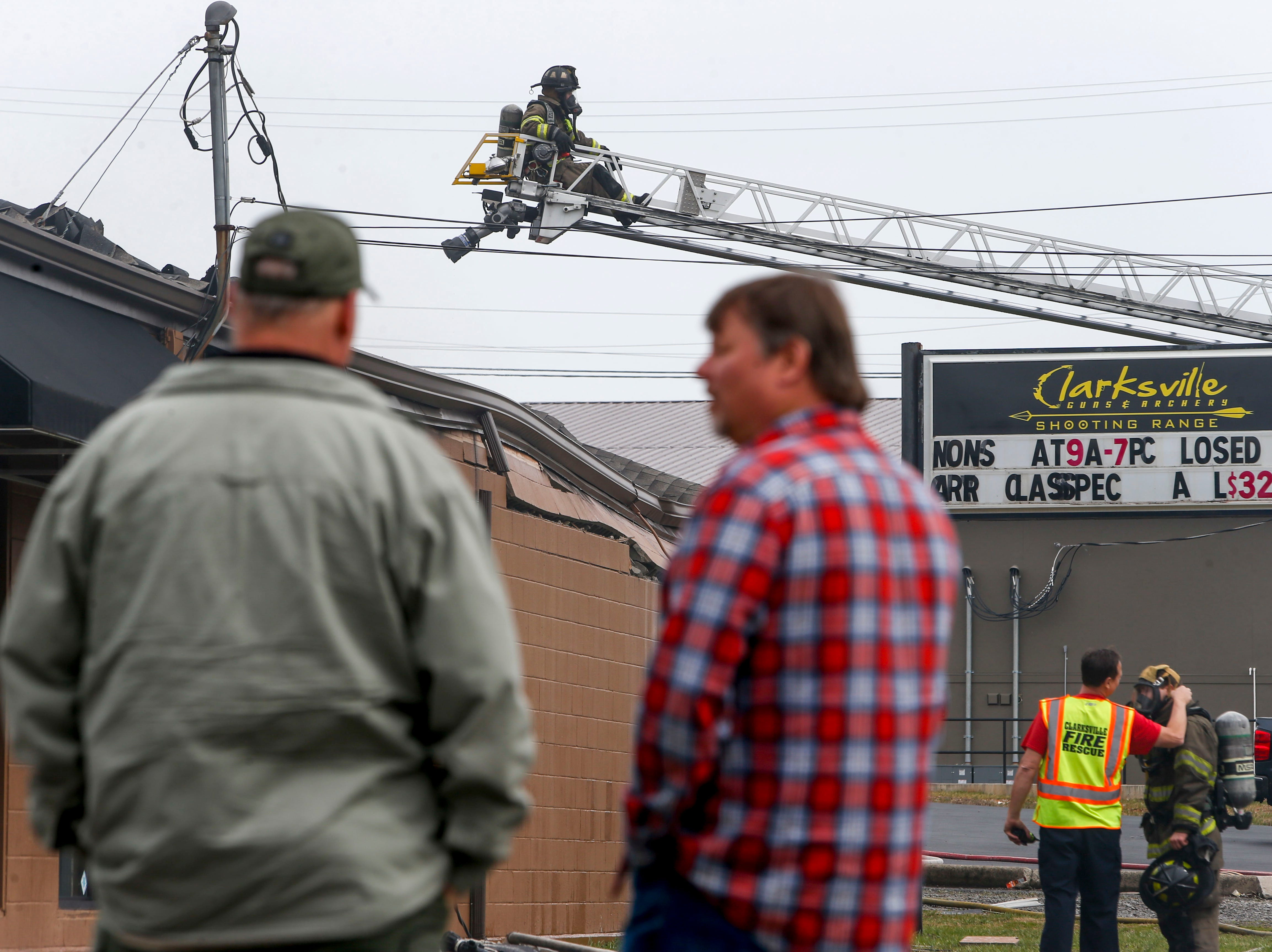 Bystanders chat with one another while Clarksville Fire Rescue works to put a fire out in the shooting range at Clarksville Guns & Archery in Clarksville, Tenn., on Tuesday, March 12, 2019.