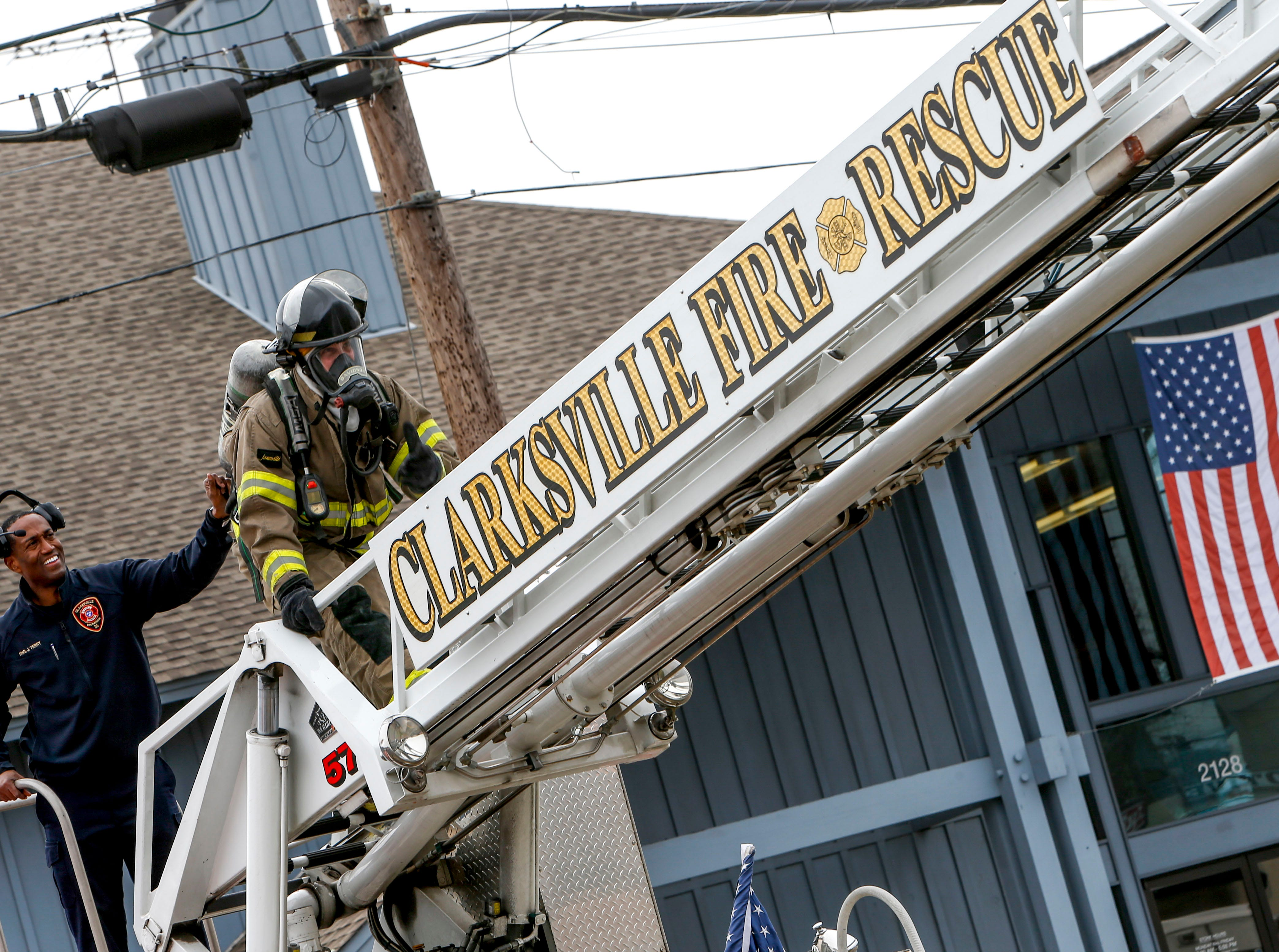 A Clarksville Fire Rescue firefighter walks across a ladder to operate a hose facing into the building at Clarksville Guns & Archery in Clarksville, Tenn., on Tuesday, March 12, 2019.