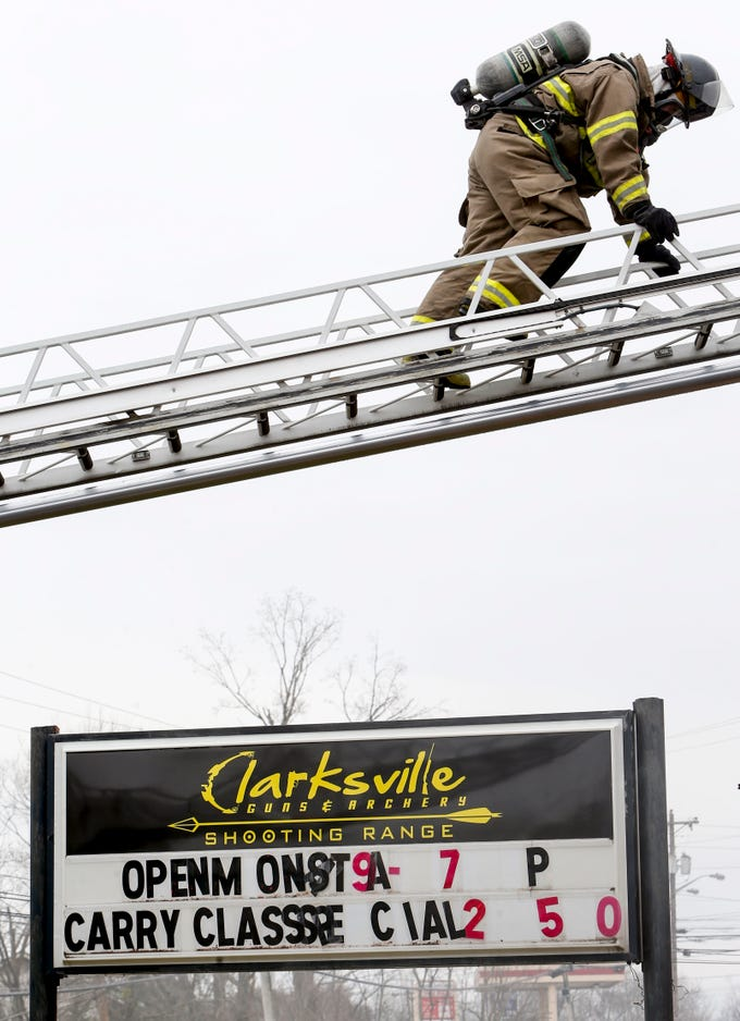 A Clarksville Fire Rescue firefighter walks across a ladder to get to a hose facing inside the building to put out a fire at Clarksville Guns & Archery in Clarksville, Tenn., on Tuesday, March 12, 2019.