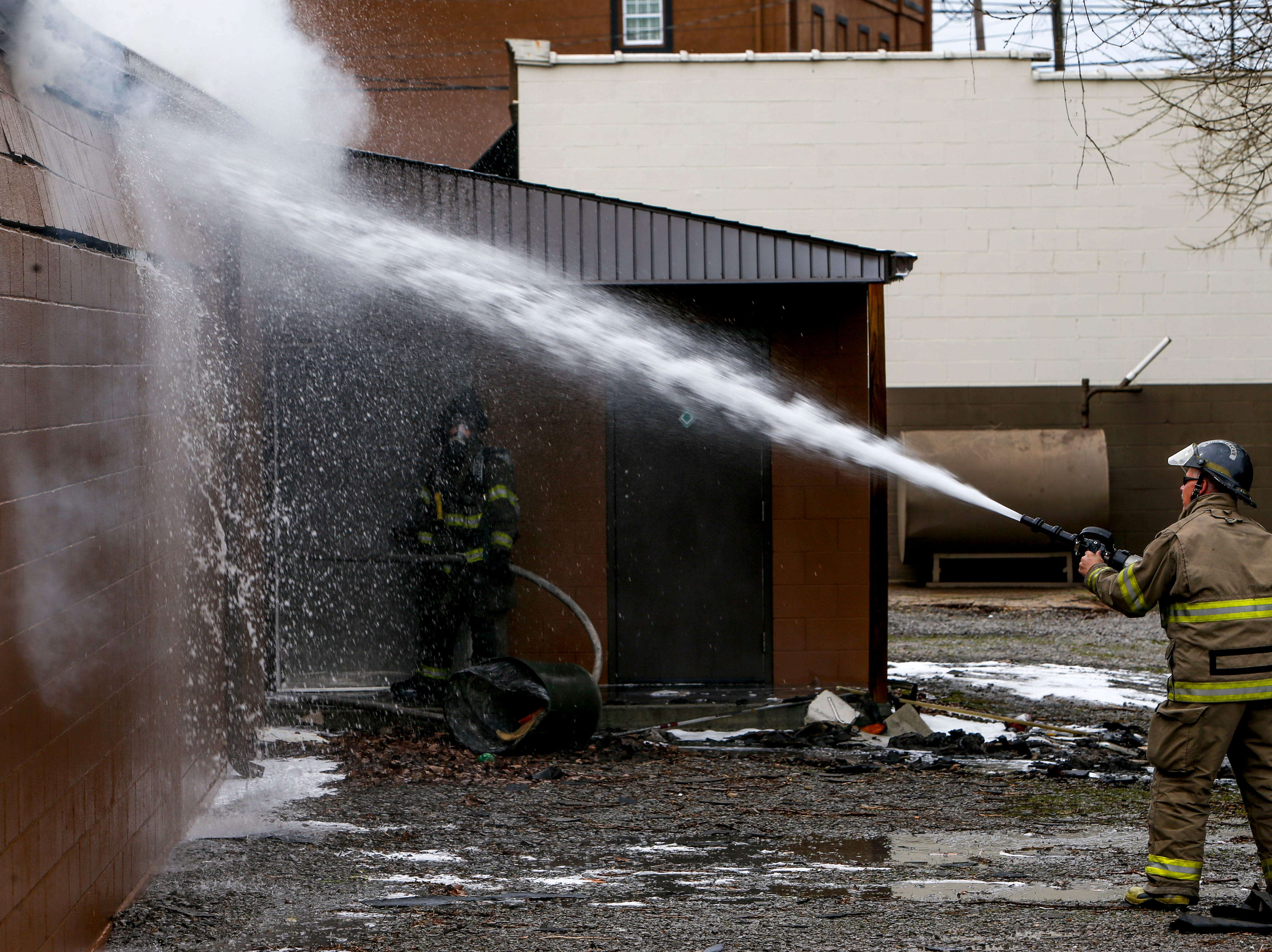 A Clarksville Fire Rescue firefighter sprays down a side wall while working to put out a fire in the shooting range at Clarksville Guns & Archery in Clarksville, Tenn., on Tuesday, March 12, 2019.