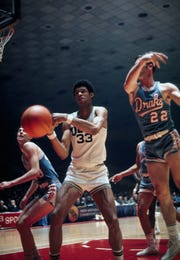UCLA center Lew Alcindor (33), who later became known as Kareem Abdul-Jabbar, fights for a loose ball against Drake University's Rick Wanamaker (43) and Gary Zeller (22) in the NCAA Final Four in 1969. UCLA defeated Drake 85-82.