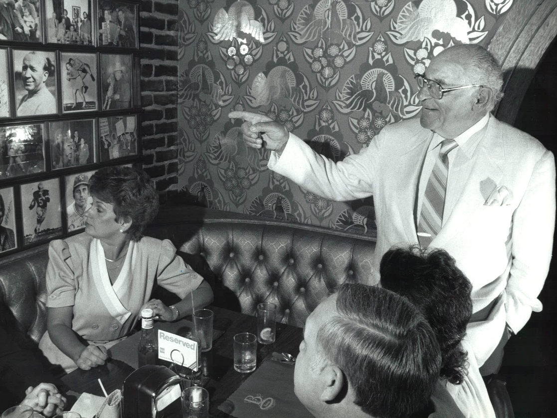 From 1986: Des Moines restaurateur Babe Bisignano explains the historic photographs in his restaurant, Babe's, to lunchtime diners.