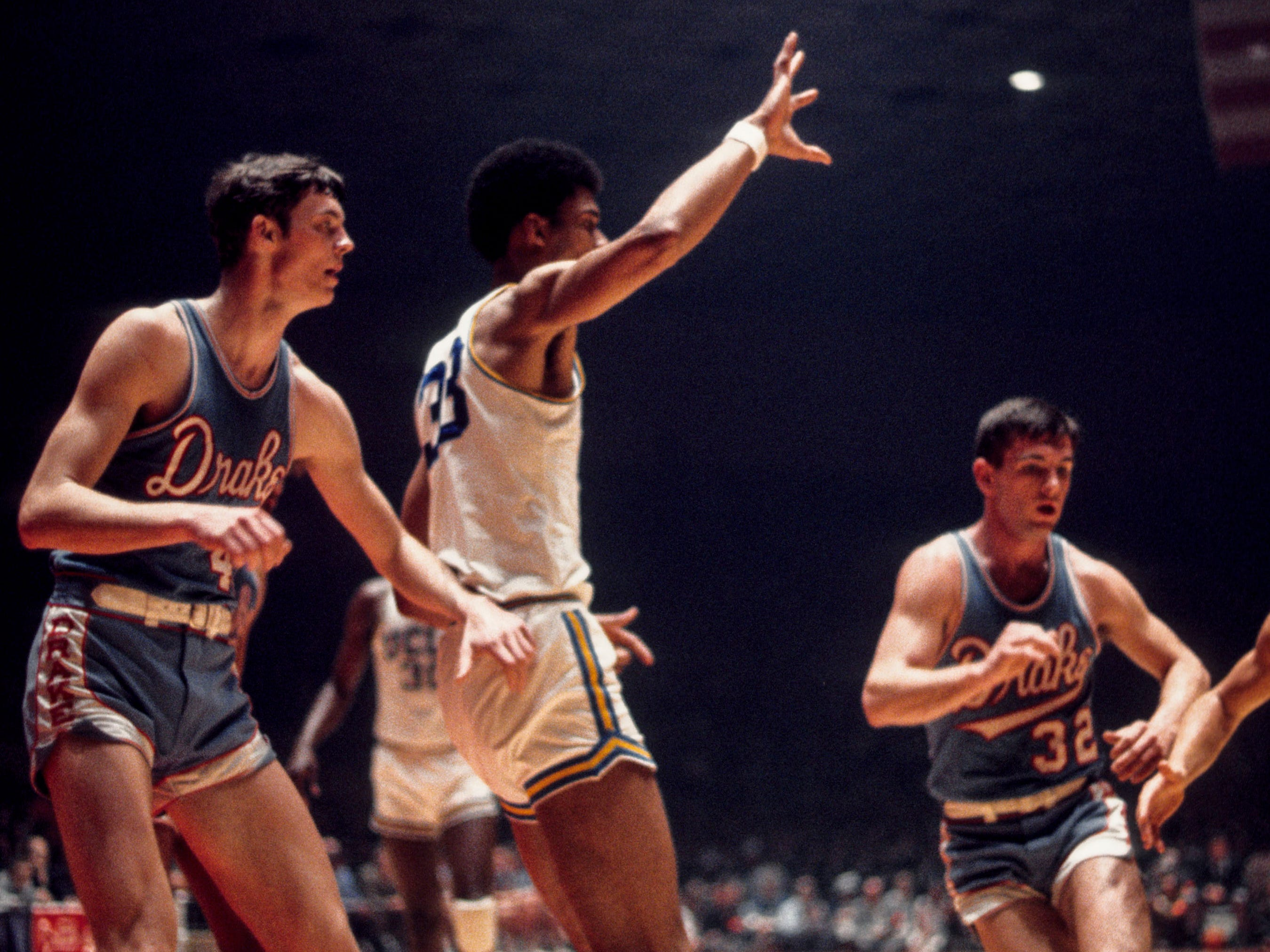 From 1969: UCLA Bruins center Lew Alcindor (33) in the post against Drake University's Rick Wanamaker, left, and  Don Draper (32) during the 1969 NCAA Tournament Final Four semifinals at Freedom Hall in Louisville, Kentucky. The Bruins defeated the Bulldogs, 85-82, and went on to win their third of seven straight NCAA titles.
