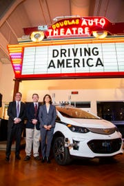 General Motors President Mark Reuss, left,  Matt Anderson and Patricia Mooridian of The Henry Ford  pose with GM's first self-driving test vehicle on Tuesday at the museum in Dearborn.