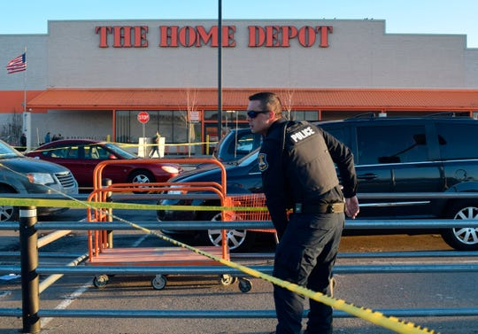 In a Monday, March 11, 2019 photo, a St. Clair Shores police officer places caution tape in the parking lot at the Home Depot in Roseville, Mich., where authorities say police shot and wounded a man who pulled a handgun at the home improvement store.